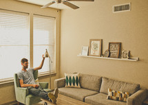 a man with his feet on a coffee table adjusting a lamp