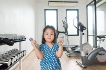 child lifting weights at the gym