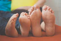 a mother and son's bare feet