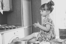toddler girl sitting on a kitchen counter