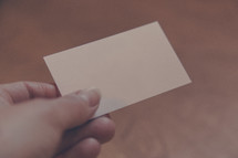hand holding out a blank business card