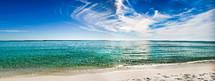 Crystal clear ocean water on a white sand beach.