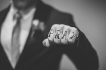 """Pray"" written on the knuckles of a man in a suit."