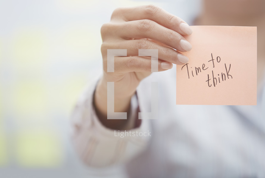 a woman holding a sticky note with the words time to think