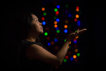 a woman looking up to God in worship and colorful bokeh lights