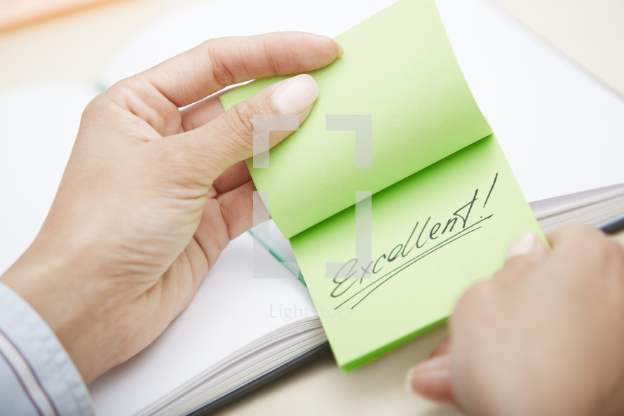 woman holding a sticky note with the word excellent