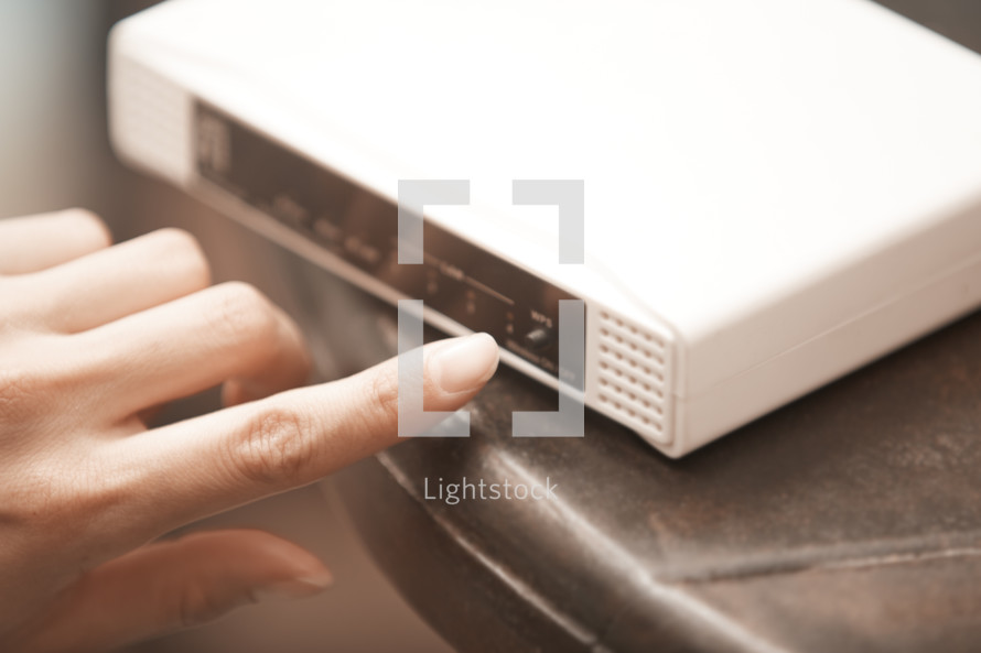 a woman resetting a modem
