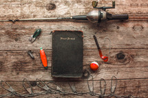 fishing pole and lures beside a Bible
