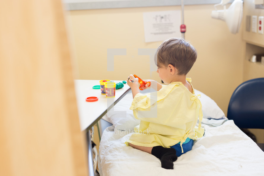 a boy child in a hospital gown playing games in a hospital bed