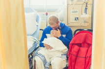 a father comforting his son in a hospital gown in a hospital