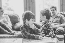 brothers in pajamas playing with cars on a coffee table