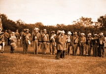 A lineup of Confederate Army Soldiers getting ready for inspection and a civil war re-enactment to illustrate history in the making for all to see and remember.