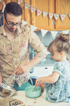 father and daughter baking in a kitchen