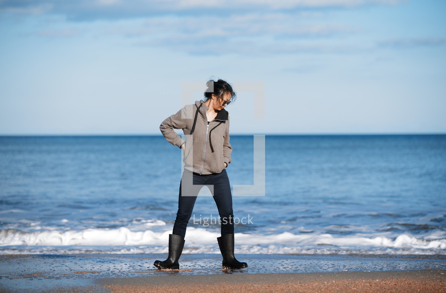 woman standing on a beach in rain boots