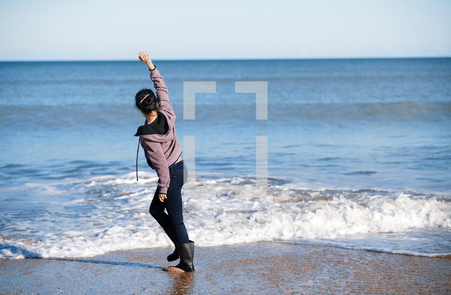woman running on a beach in rain boots