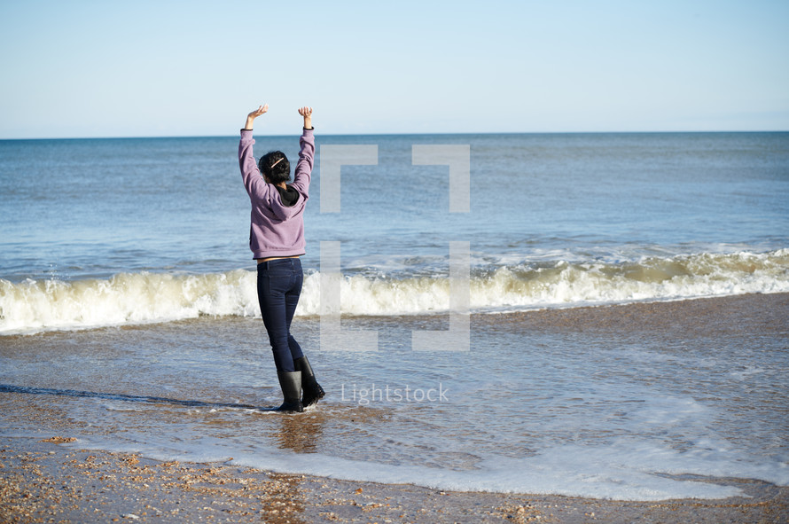 woman standing on a beach wearing rain boots