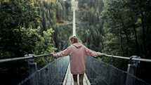 a woman crossing a swinging bridge
