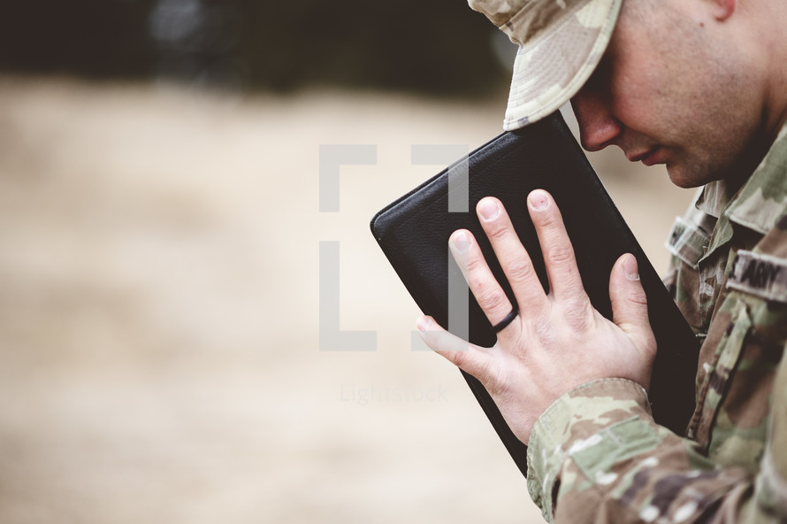 soldier holding a Bible praying