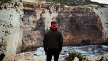 a man looking out at sea cliffs