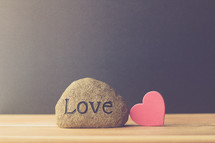 a rock with the word love and red heart