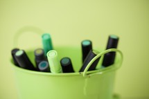 green markers in a bucket
