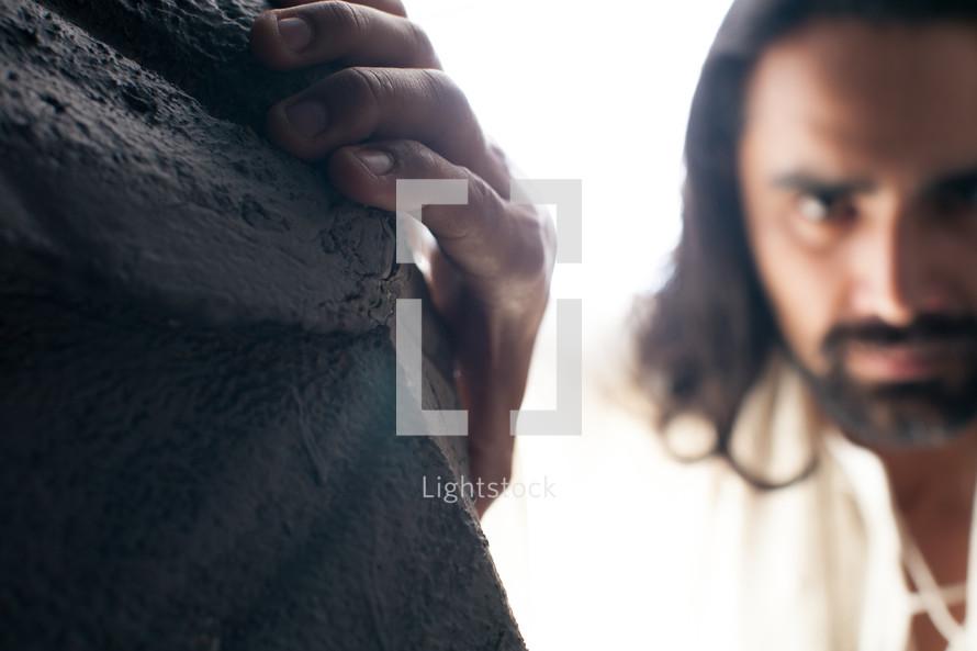 Jesus grabbing a rock wall.
