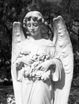 A tall and ornate statue of an angelic female figure stands in a historic cemetery in the southern United States of America where many historic figures are buried and serves as a historic landmark.