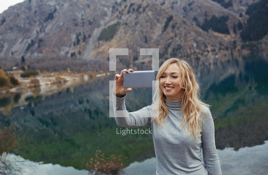 a woman taking a selfie standing in front of a lake