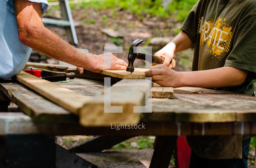 boy hammering a nail into wood