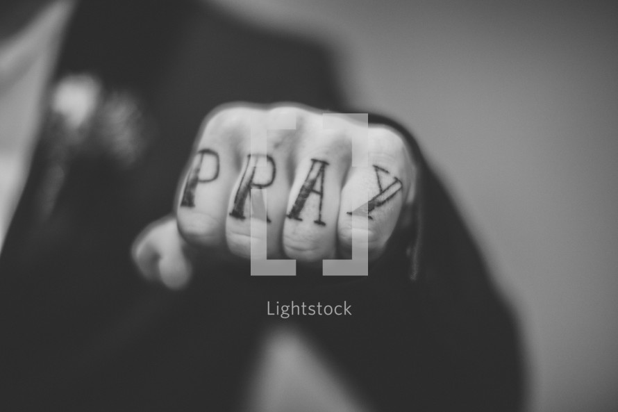 """""""Pray"""" written on the knuckles of a man's hand."""