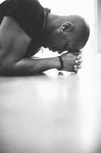man kneeling in prayer with his hands and forehead on the ground