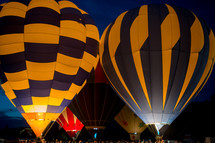Hot air balloons lit up at a festival.