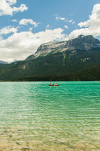 people in a canoe on a mountain lake