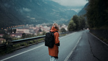 a young woman in a trench coat and backpack standing in the middle of a road