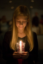 A child holding a candle at a Christmas eve worship service.