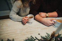 a couple sitting at a table having coffee