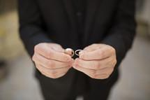 groom holding wedding bands