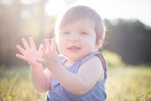 toddler girl sitting in bright sunlight clapping hands