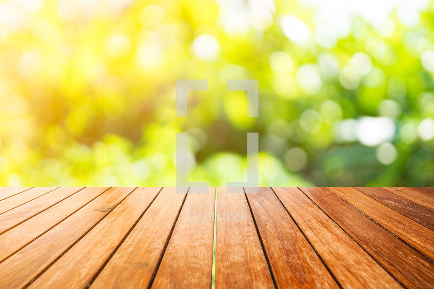 wood decking and bokeh sunlight on green leaves