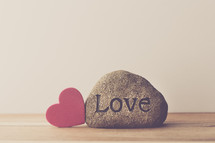 a rock with the word love and a red heart