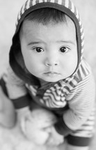Infant child in a hoodie sitting on the floor.