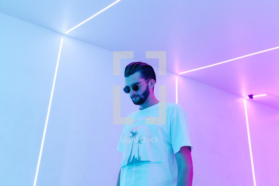 man standing in a purple hallway