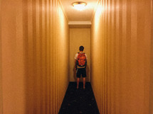 man with a backpack standing at the end of a hallway