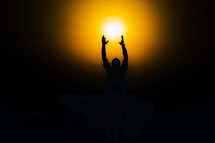 silhouette of a man reaching for the sun