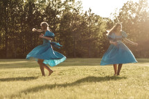 Two young women in blue dresses dancing in a field.