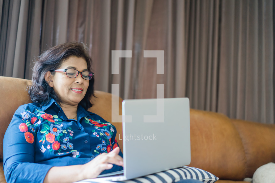 a woman sitting on a couch working on a laptop computer