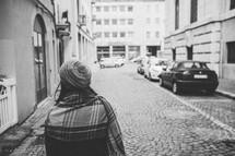 a woman in a coat and shawl walking along a narrow street window shopping