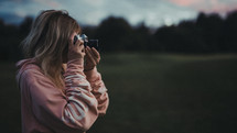 a woman taking a picture with a camera at sunset