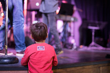 a child watching musicians perform on stage