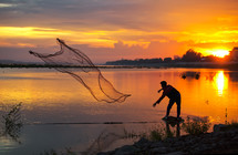 A man casting a net at sunset
